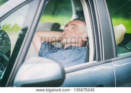 Man sleeping in the car before next part of the journey