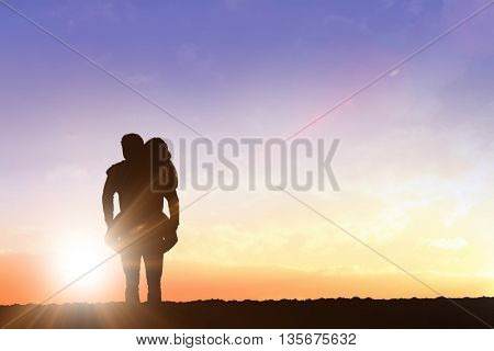 Handsome man giving piggy back to his girlfriend against clouds