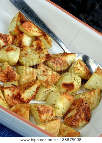 Closeup of  golden brown roasted potatoes in dish with serving spoon.