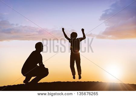 Smiling boy jumping against clouds