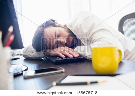 A man sleeping on his desk in the office