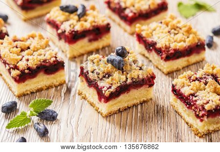 Honeysuckle Crumb Cake  sliced into pieces on a light background with berries of honeysuckle and flowers