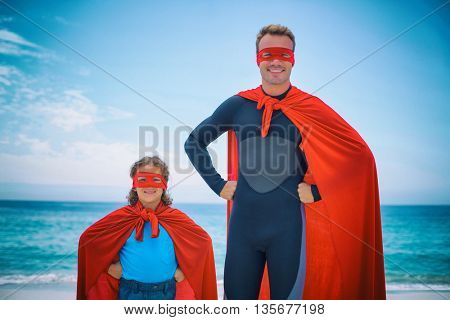 Portrait of father and son in superhero costume standing at sea shore