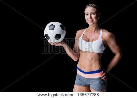 Female athlete holding a soccer ball on black background