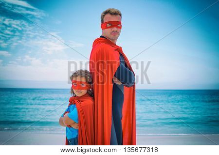 Portrait of confident man and son standing back to back sea shore