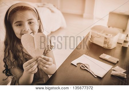 High angle portrait of a cute young girl holding heartshape paper at table