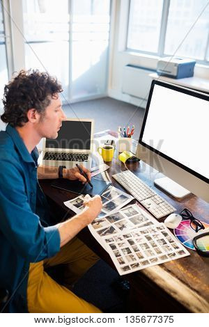 A man working on his computer while looking at books