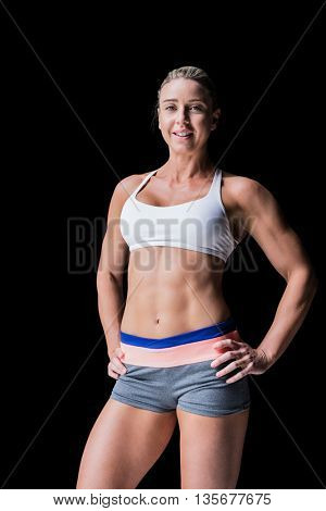 Female athlete posing with hands on hip on black background