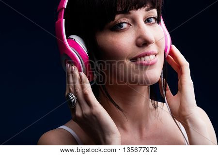 Grinning Young Adult Female Using Headphones