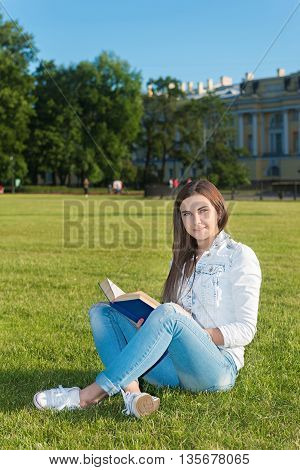 Smiling beautiful young woman on grass and reading book against background of summer green park.