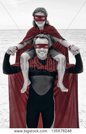 Portrait of happy father in superhero costume carrying son on shoulder at beach