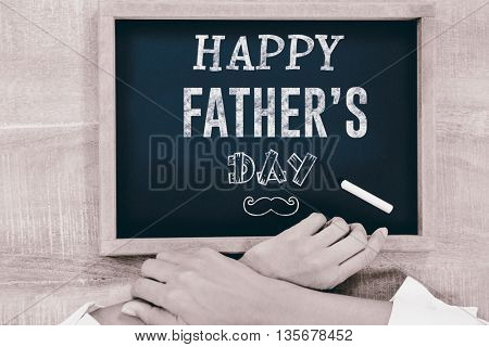 Fathers day greeting against hand writing on chalkboard