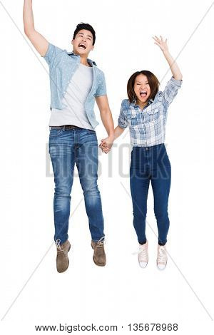Excited young couple holding hands and jumping on white background