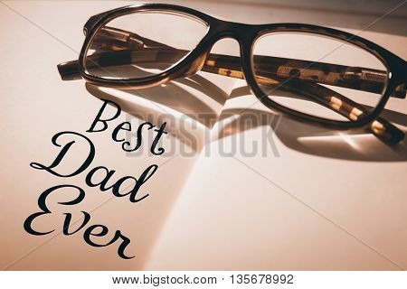 Word best dad ever on a white background against plastic eyeglasses on blank book