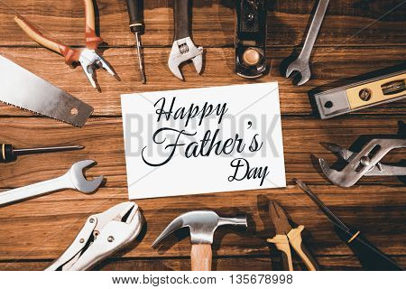 Happy fathers day message surrounded by tools on wooden background