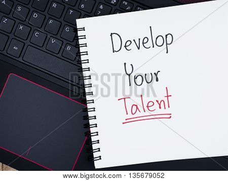 Handwriting Develop Your Talent on blank notebook with laptop keyboard. (Business concept)