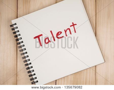 Handwriting Talent on blank notebook with wood background. (Business concept)