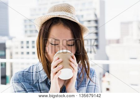 Young woman having coffee outdoors