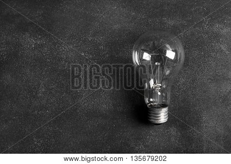 Transparent electric bulb on the black chalkboard (image has copy space for your imafe or text)