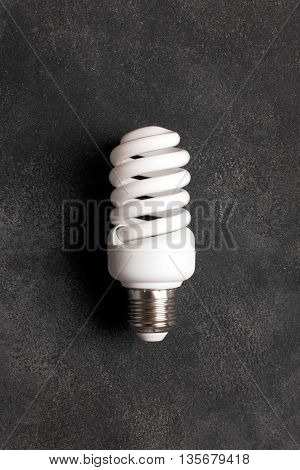 Energy saving electric bulb on the black chalkboard (could be used as a concept of using pure energy)