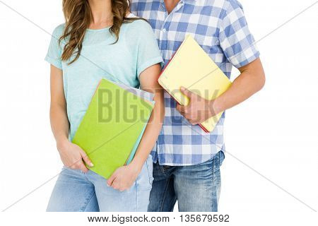 Mid section of young couple holding book and folder on white background