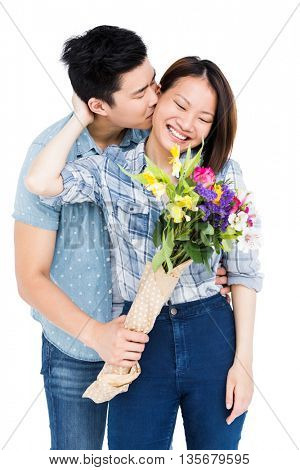Man kissing woman and giving her flowers on white background