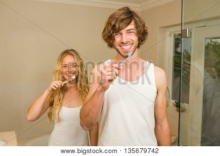 Cute couple brushing their teeth together in the bathroom