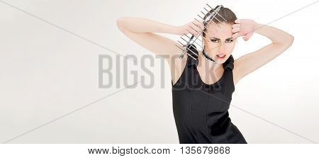 young girl keep kitchen tool on her head in studio