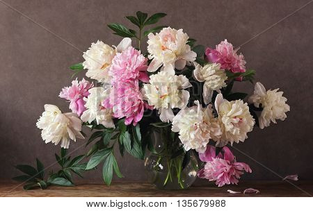 Still life with a bouquet of peonies in a glass jug on a dark background.