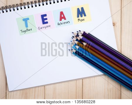 Word spelling TEAM and handwriting together everyone achieve more on notebook with wood background (Business Concept)