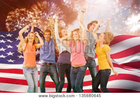Friends partying together while laughing and smiling against colourful fireworks exploding on black background