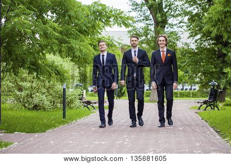 Three young men in elegant business suits walking in summer street, outdoors