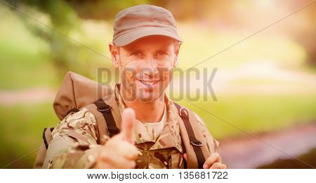 Portrait of happy army man with thumbs up standing in park