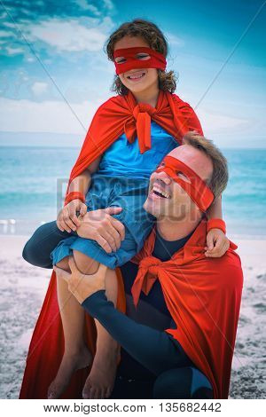 Father in superhero costume smiling while carrying son on shoulder at beach