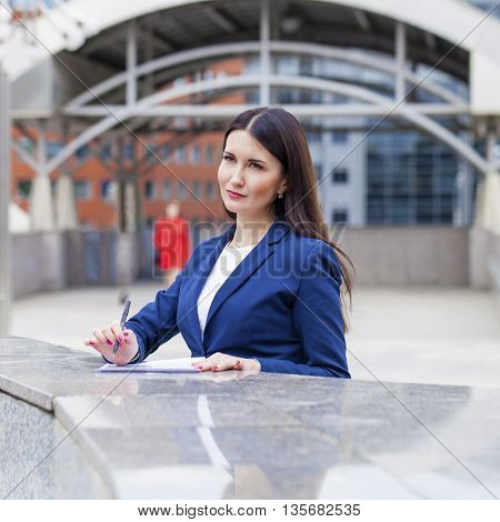 Young beautiful business woman in a blue jacket signs the contract, summer street outdoors
