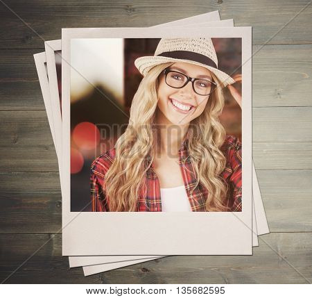 Gorgeous smiling blonde hipster posing against bleached wooden planks background