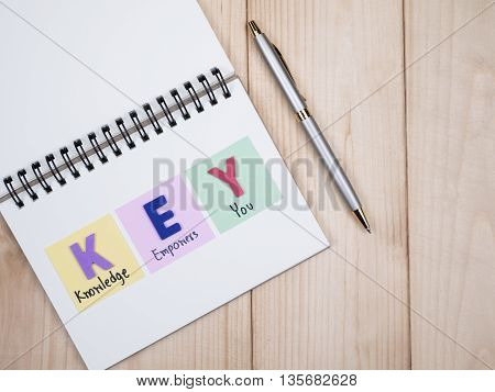 Word spell KEY and handwriting word Knowledge Empower You and pen on notebook with wood background