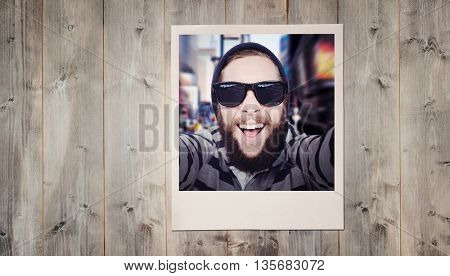 Happy hipster against wooden fence against pale wooden planks