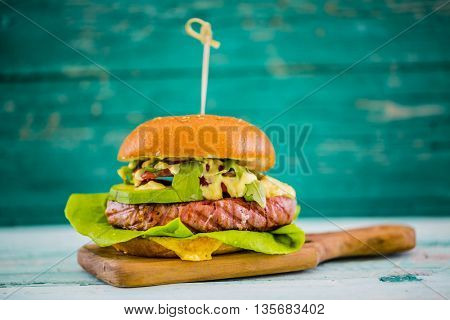 Tasty grilled tuna burger with lettuce and mayonnaise served on wooden table