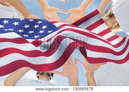 Volunteers with hands together against blue sky against focus on usa flag