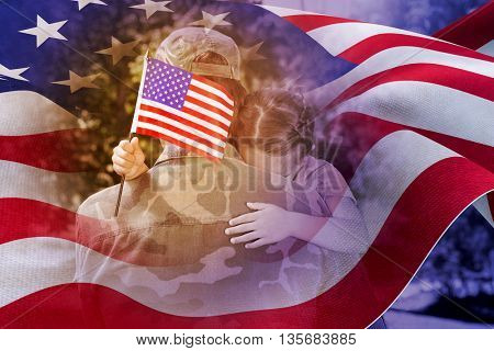 Army man hugging daughter with American flag against focus on usa flag
