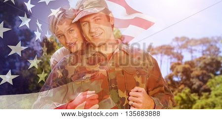 Portrait of simling army man with wife against focus on usa flag