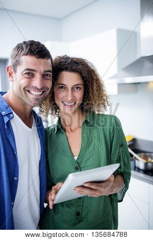 Portrait of couple using digital tablet in kitchen at home