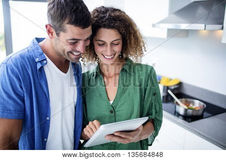 Happy couple using digital tablet in kitchen at home