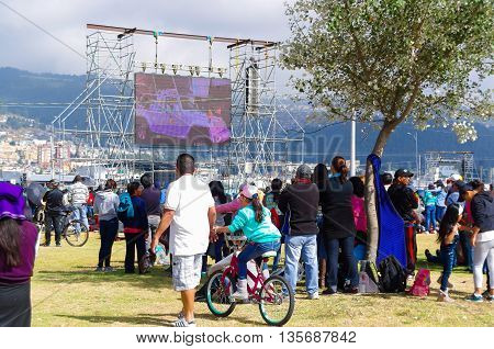 QUITO, ECUADOR - JULY 7, 2015: People looking in a big screen the little road that pope Francisco made around the mass in Ecuador.