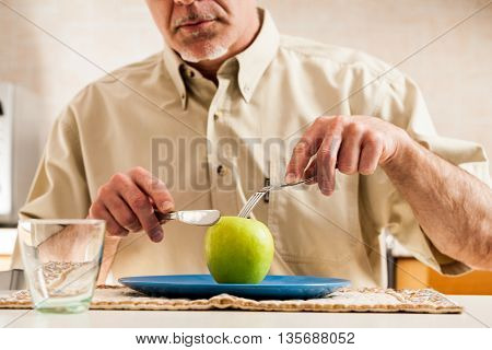 Obscured Man Slicing Apple Over Blue Plate