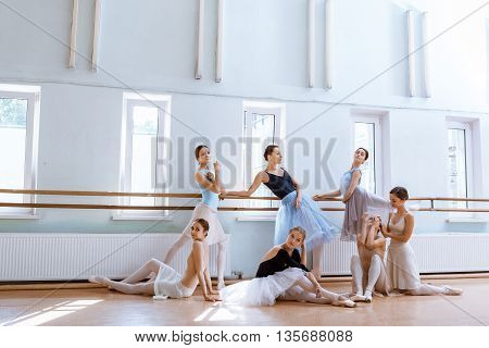 The seven ballerinas at ballet rack in the rehearsal hall of the theater