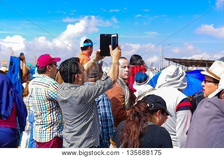 QUITO, ECUADOR - JULY 7, 2015: A young man holding a mobile phone, trying to fim pope Francisco over heads, mass event.
