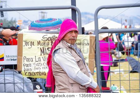 QUITO, ECUADOR - JULY 7, 2015: Man looking to the camera, covered by pink sweater on his head, pope Francisco mass.