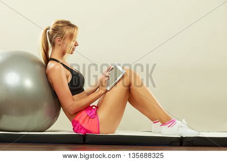 Fit Woman Sitting On Floor With Tablet Pc